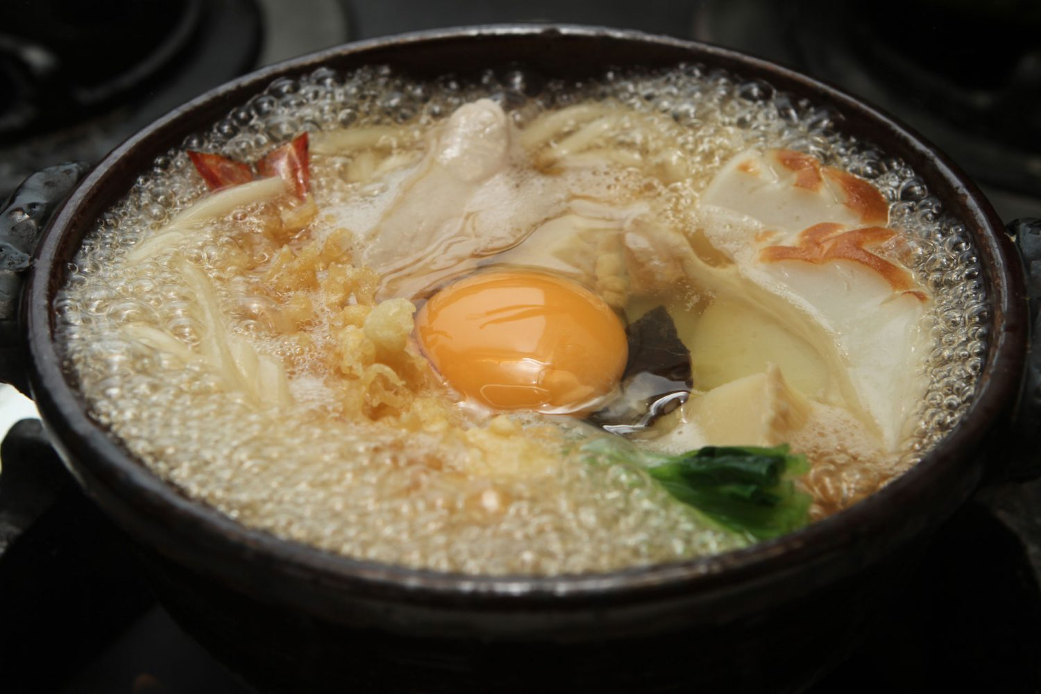 NABE-YAKI(鍋焼き) : Noodles cooked with vegetables, a fried prawn, chicken & raw egg served in earthen-ware casserole